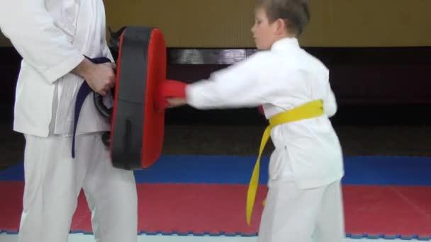 Piros csíkokkal a kezén, egy mozgásban lévő atléta üti az ütéseket a kezével a szimulátoron.