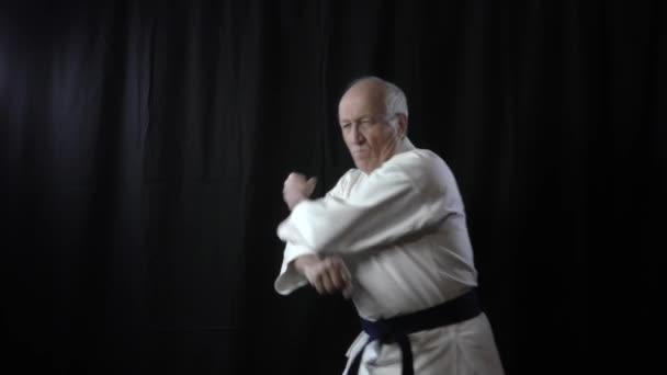 Fekete alapon, egy öreg férfi atléta gyakorolja a blokkokat és a karokat.