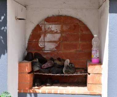 Furnas, Azores - 23rd April 2019:BBQ chimney with shoes on the grate
