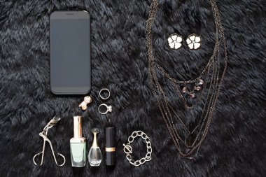 Mobile device in black color with beaty essential on black, Beau