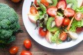 Fresh salad with strawberries, kiwi, tomatoes and apples, top vi