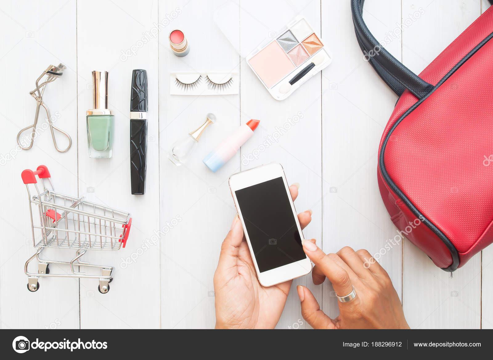 7965ebc4a7fc0b Frau Hand berühren Bildschirm auf mobilen Gerät mit Warenkorb und Kosmetik  auf hölzernen Hintergrund, kreative flach legen Online-shopping-Konzept– ...
