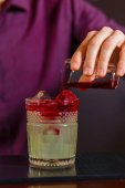 The bartender making New York sour cocktail
