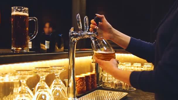 A pultos nő sört önt a tiszta magas pohárba egy stílusos bárban, közelről. A kék pulcsis szakember kinyitja a csapot a kezénél fogva, és a sör fehér habbal áramlik a bögrében..