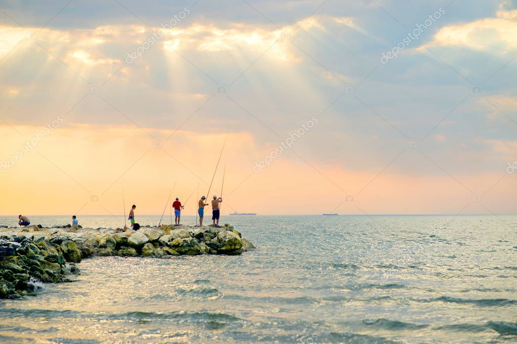 Fisherman at lake on sunset