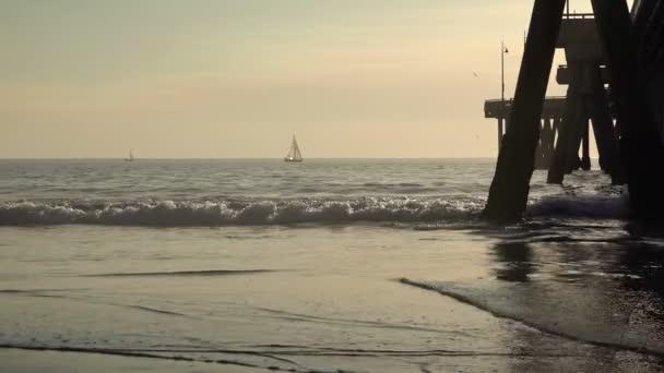 Víz visszaverődik a homokon az óceán mólójánál egy vitorlással a távolban, lassított felvétel