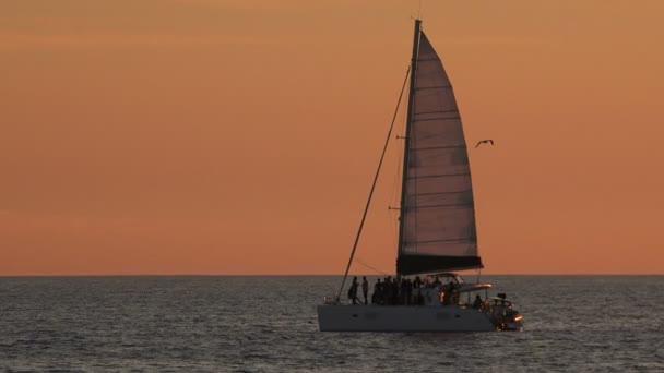 Plachetnice v oceánu při západu slunce