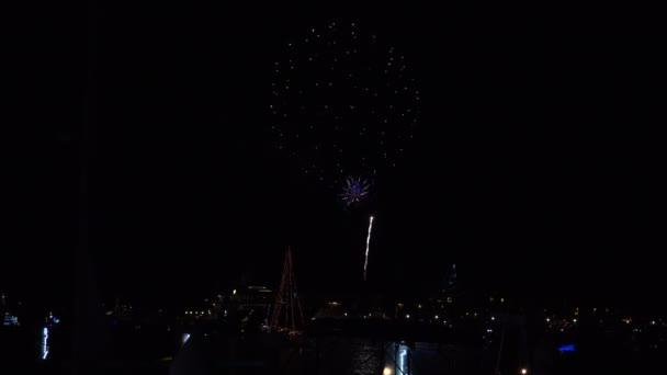 Tűzijáték tör ki a kikötőben, miközben a karácsonyi fényben díszített vitorlások alatta utaznak.