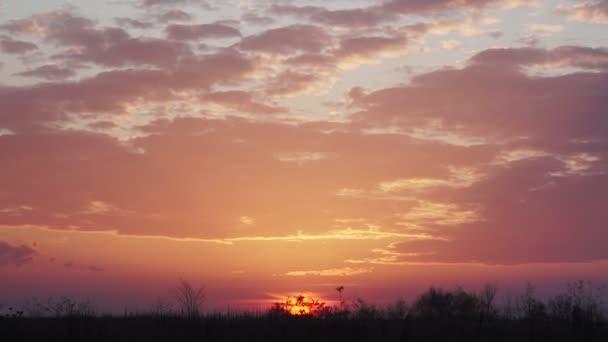 Oranžové až červené načechrané mraky se za soumraku valí proti zářivému modrému západu slunce. Podzimní malebné nebe