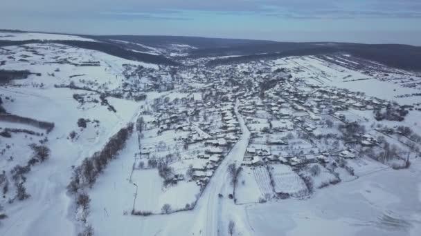 Letecký pohled na obec mezi poli a lesy v zimě. Zimní krajina zasněžené pole a stromy v krajině.
