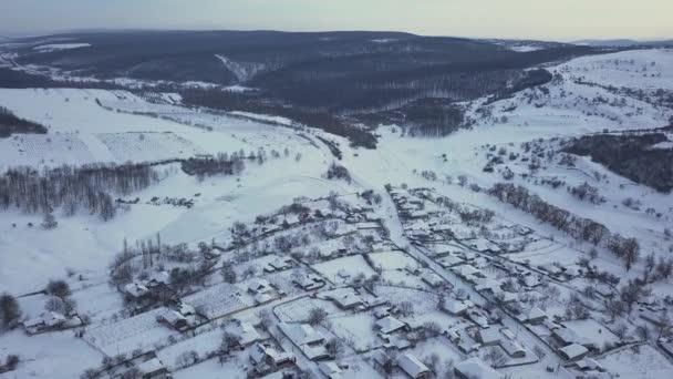 letecký pohled vesnice mezi poli a lesy v zimě. zimní krajina zasněžené pole a stromy na venkově.