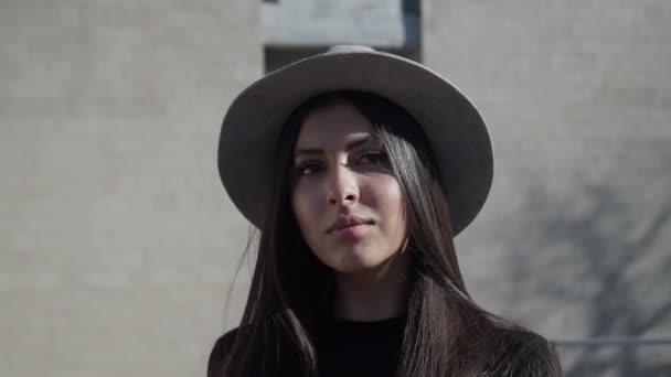 Portrait of a glamorous girl in a hat on the street