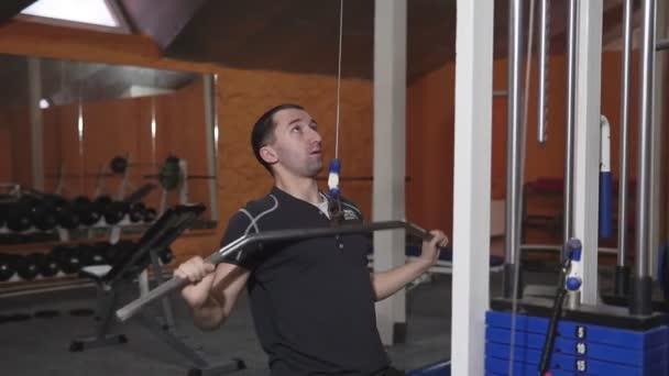 Guy kulturista v tělocvičně, pracuje s barem, které je třeba utáhnout, zlepšení triceps, velký prsní sval a přední deltový sval. Koncept milovat sporty, jít do posilovny jíst pravé štíhlé tělo být zdravý