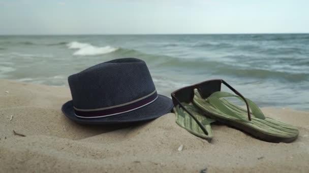Příslušenství pro pláž ležící na písku, pánské pantofle a sluneční brýle na pláži