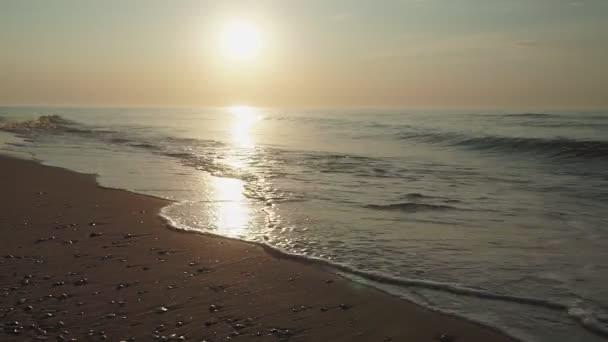 silueta muže, který mírumilovně kráčí po opuštěné pláži za úsvitu. přímořská