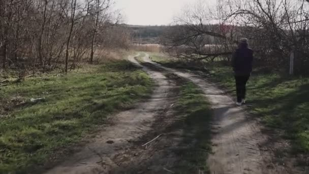 A young woman is walking along a country road and talking on the phone