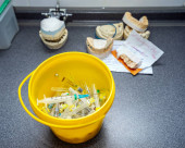 Medical waste, syringes with needles and empty vials in the trash bucket closeup. Dental forms and models with prosthetic teeth in the background