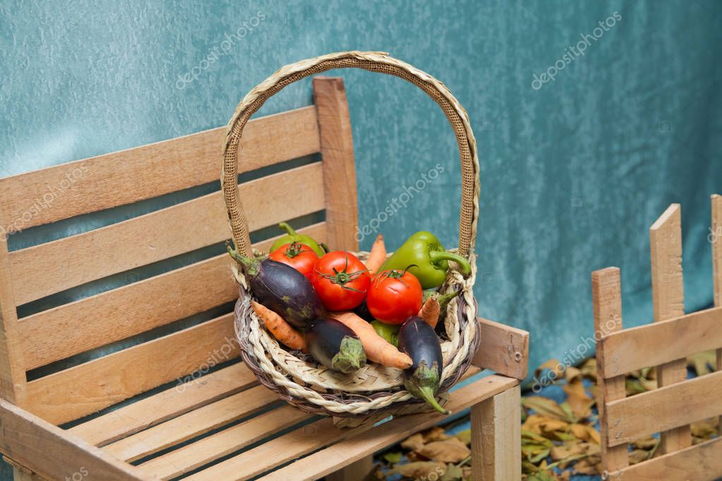 Autumn fruit in the basket. Tomato, pepper, markof, eggplant. Bench to the right. Autumn scene.