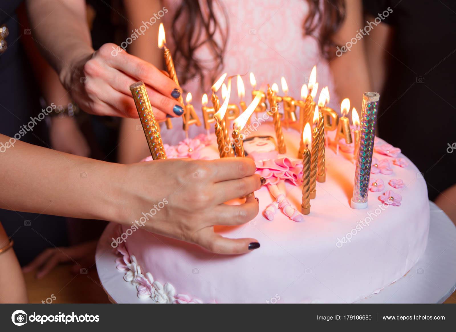 Они горят свечи на день рождения. Праздничный торт со свечами.