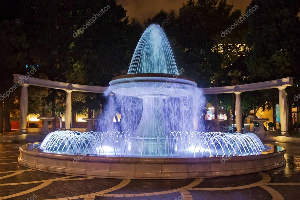 The fountain in the city center. View to crowded street and people in Baku Azerbaijan . night vision of a round park Fountains square