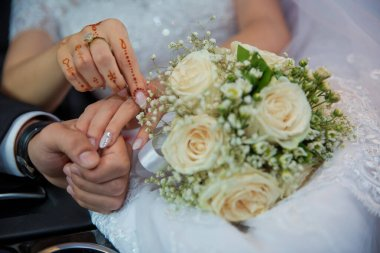 Bride and groom hands with wedding rings and bridal dress . Bride and groom's hands with wedding rings . Wedding couple holding hands .