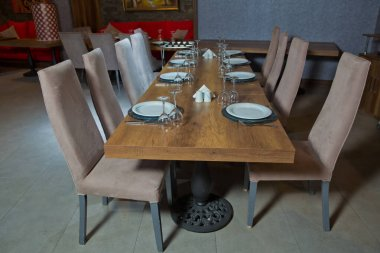 Served holiday table, cutlery, glasses, plate, fork . Set of a dish with spoon, fork and knife on wooden table. Empty Table setting on woo den table in restaurant served for dinner . Brown chare