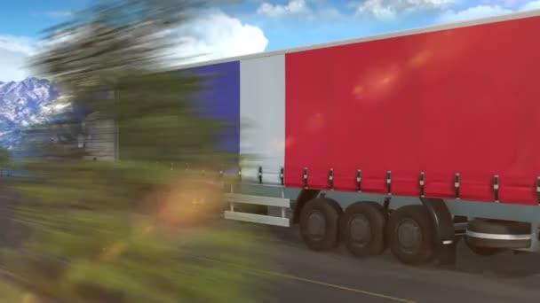 Vlajka Francie vyvěšená na boku velkého nákladního auta jedoucího po dálnici