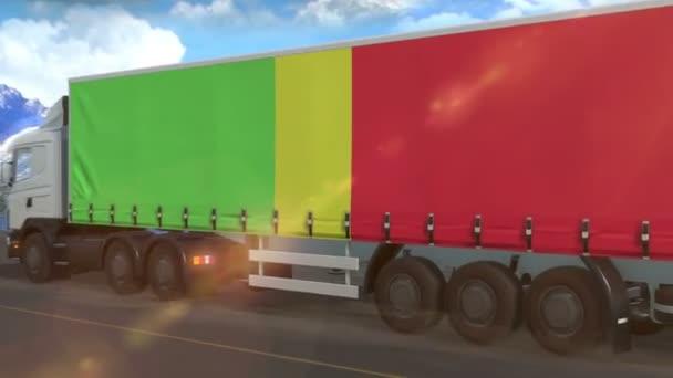 Vlajka Mali vyvěšená na boku velkého náklaďáku jedoucího po dálnici