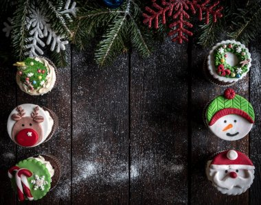 Christmas cup cakes served on the wooden table with blank space