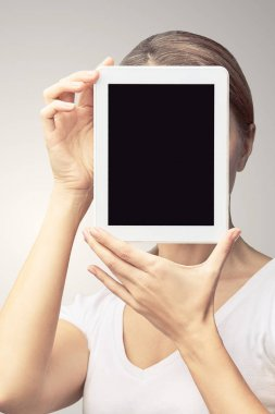 Girl holding computer pad. Mock up at tablet black screen. Face near laptop. Woman showing pc