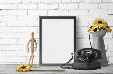 empty photo frame with yellow daisies in metal garden jug and retro phone