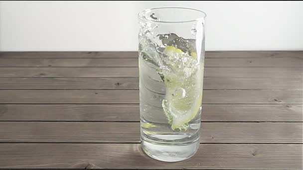 Piece of lemon falling down into transparent glass of mineral water with mint. Water splashes in the glass.