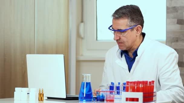 Vědec psaní na přenosném počítači v biochemii Lab. vědec provádí chemický výzkum v chemické laboratoři