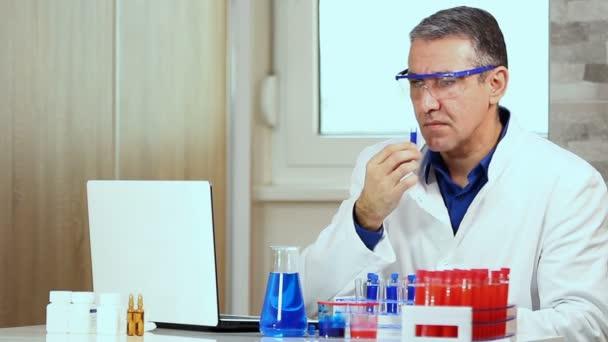 A középkorú kémikus elemzése kémcsőbe folyékony. Tudós végzett kémiai kutatás kémia labor. Gépelés-on laptop számítógép biokémiai Lab tudós.