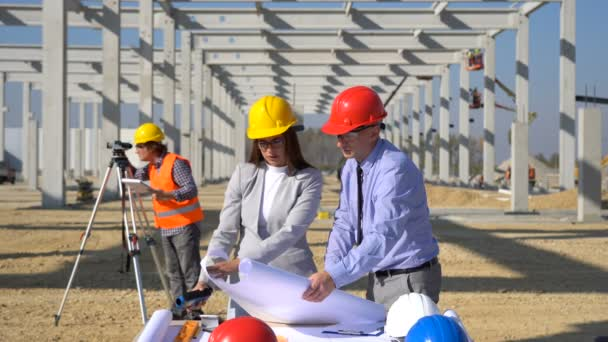 Engineer, Architect and Mature Businessman Checking the Construction Blueprint. Business, Building, Teamwork and People Concept. Construction Business Team at Construction Site. Project Management and Field Crew Meeting on Construction Site.