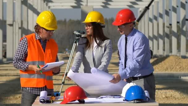 Podnikatel, Inženýr a Ženská Architektka Kontrolují Stavební plán. Vedení projektu a setkání terénní posádky na staveništi.