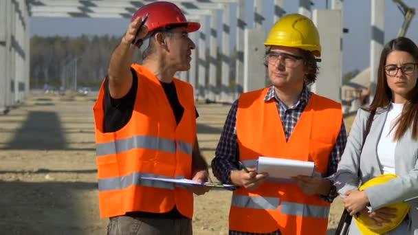 Bautrupp in Hardhats bespricht ein Projekt auf der Baustelle. Projektmanagement und Außendienst treffen sich auf der Baustelle. Supervisor, Architekt, Vorarbeiter und Bauarbeiter.