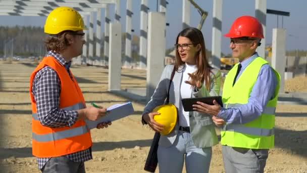 Architekt, Polier und Bauarbeiter im Gespräch auf der Baustelle. Business, Building, Teamwork und People-Konzept. Projektmanagement und Außendienst treffen sich auf der Baustelle.