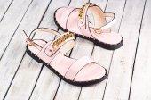Dámské letní sandály na dřevěné pozadí