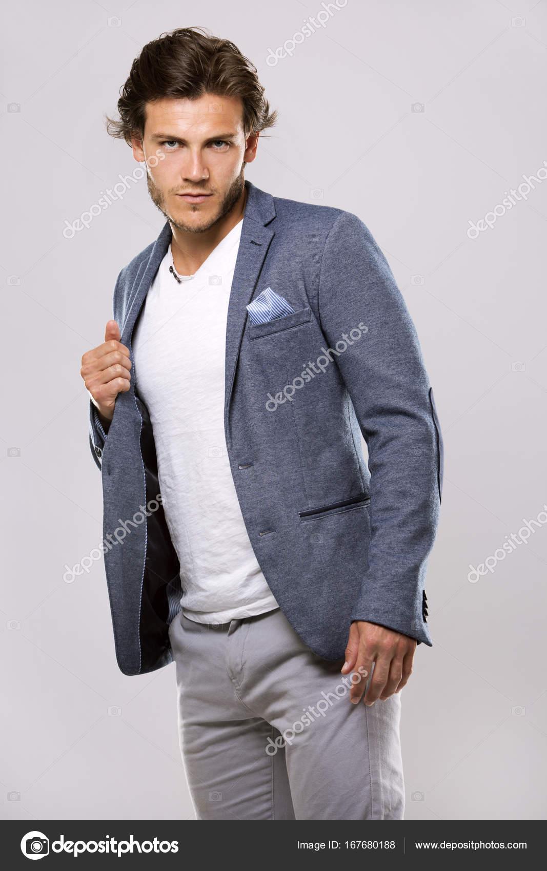 Moda ritratto di un uomo bello con taglio di capelli alla moda in una giacca  elegante su priorità bassa chiara — Foto di zdenkam 32c8f917b93