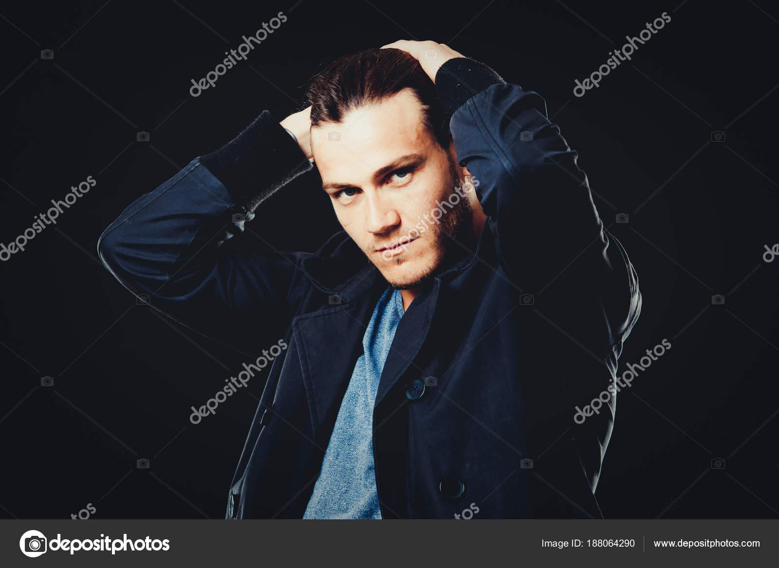 Fronte del primo piano di giovane uomo barbuta su sfondo scuro moderna e  drammatica foto. Modello maschio Caucausian indossa una maglietta blu e  giacca nera ... b23d64a0eaa