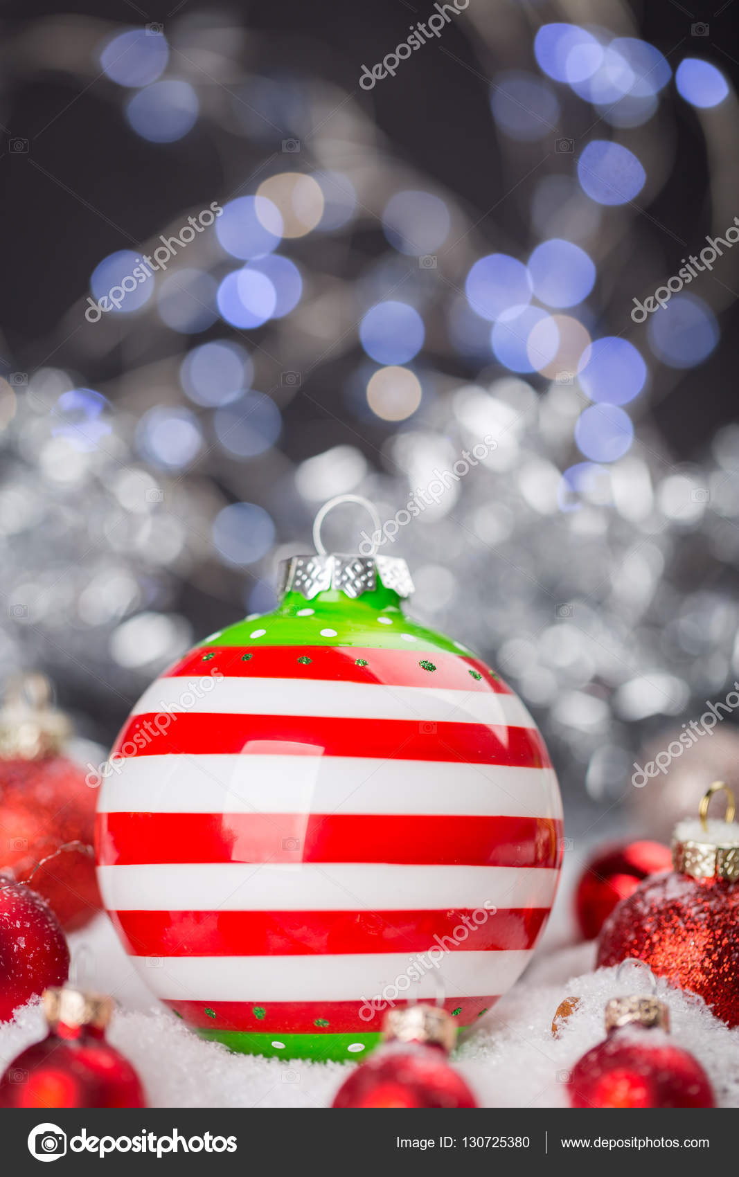 close up still life of red christmas ball decoration with painted white snowflakes surrounded by shiny red globes on dark gray background with copy space