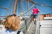 Lidé, chůzi do schodů na palubě lodi, zadní pohled