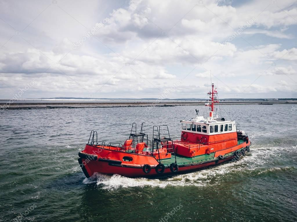 Red tugboat sailing by sea