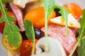 Kreatív összetételét összetevők paradicsom, sajt, szalámi, gomba, sült saláta kitûnõ, olajbogyó formájában egy szelet pizza