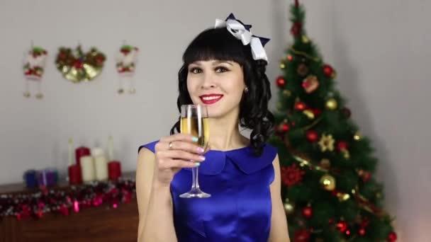 Dívka se sklenicí vína na vánoční stromeček. Krásná bruneta dívka v modrých šatech pije šampaňské a úsměvy v době Vánoc