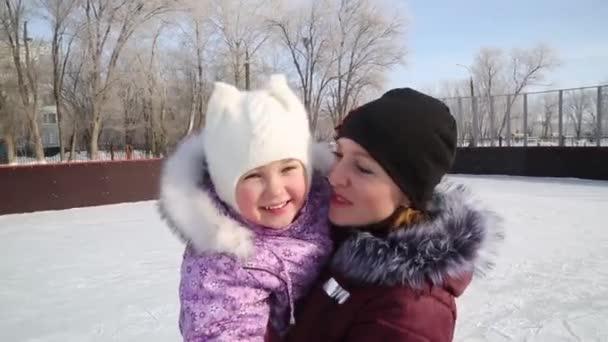 mama umarmt ihre schöne tochter im winter auf der rink.a junge mutter und kleine tochter umarmen und küssen sich auf einem winterspaziergang.