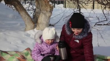 Mom and daughter drink tea from a thermos on a picnic.A young mother and beautiful little daughter are sitting on a rug under a tree and drinking tea in the winter.