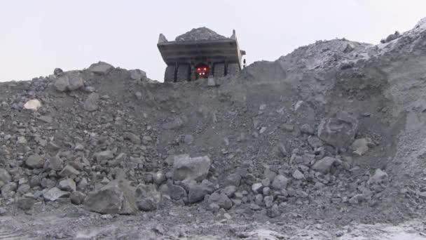 Velké dump truck vylévá 50 tun rudy do útesu. Z těla vozu v kariéře kameny pour