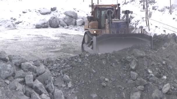 Buldozer funguje v kariéře v zimě. Traktor s kopečkem na pracovním místě lomu nerostů.